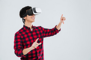 Asian man dressed in casual shirt in a cage and wearing virtual reality device and pointing. Isolated over white background.