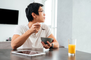 Asian man in kitchen. looking away. with cereal, tablet and juice. sitting by the table