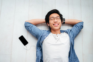 Asian man in shirt on the floor. with phone. listening music. looking at camera