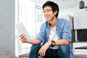 Asian man in shirt with tablet siitng on sofa