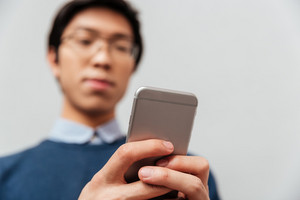 Asian man looking at the phone. gray background