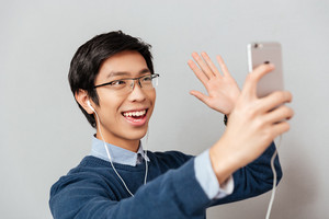 Asian man waving in phone. model in glasses