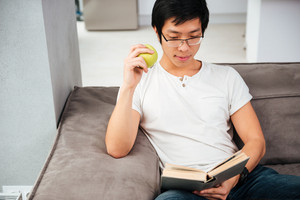 Asian man with book on sofa. so smart