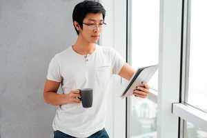 Asian man with coffee and tablet near the window