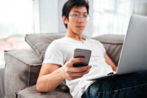 Asian man with laptop and phone on sofa. side view