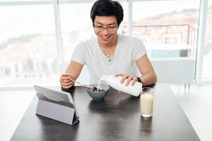 Asian man with milk and tablet. sitting by the table