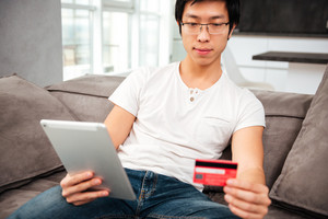 Asian man with tablet and card on sofa. front view
