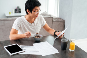 Asian man working and eating by the table. with juice, tablet and documents