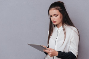 Asian pretty model reading on tablet computer. Isolated gray background