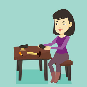 Asian shoemaker working with a shoe in workshop. Smiling shoemaker repairing a shoe in workshop. Young shoemaker making handmade shoes in workshop. Vector flat design illustration. Square layout.