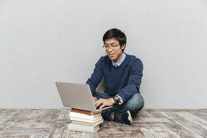 Asian student sitting on the floor. with laptop and books