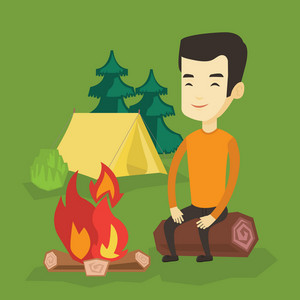 Asian travelling man sitting near a campfire at a campsite. Young travelling man sitting on a log near a campfire. Tourist relaxing near campfire. Vector flat design illustration. Square layout.