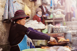 Asian woman selling sausages on traditional street market in Sapa, Vietnam.