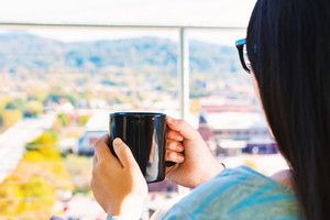 Asian woman with a black cup of coffee on her balcony