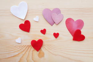 Assorted hand crafted felt and paper hearts on natural wood background