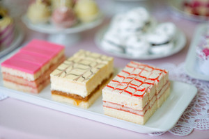 Assortment of different mini cakes with cream laid on white plate. Table with pink tablecloth and handmade lace.