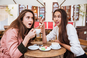 Astonished girls in coats. at cafe. drinks coffee
