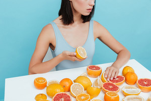 at the table with oranges and grapefruits over blue background