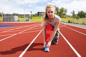 Athletic female runner tying shoelaces on running track