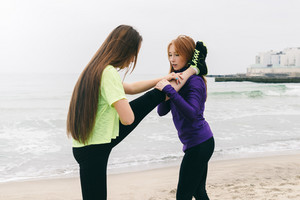 Athletic girl in sportswear help each other to do stretching on the beach on a cloudy day. A healthy lifestyle outdoors.