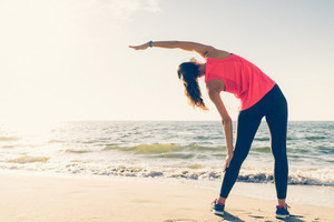 Athletic girl on the beach in the headphones makes stretching in the morning