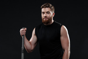 Athletic man with barbell. side view. looking at camera. isolated dark background