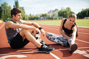 Athletic young couple sitting and stretching legs together on stadium