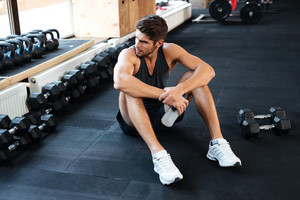 Atletic man sitting down in gym and looking away