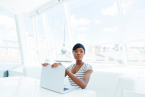Attractive african american young woman accountant working in office using laptop