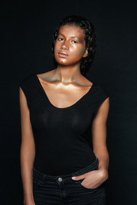 Attractive african american young woman in black top over dark background