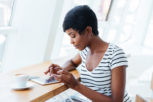 Attractive african businesswoman using tablet amd having coffee break in office