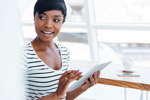 Attractive afro american businesswoman holding tablet computer and looking away in office