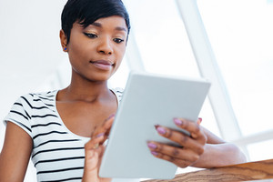 Attractive afro american businesswoman using tablet computer in office