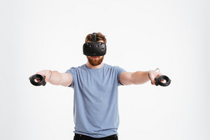 Attractive bearded man wearing virtual reality device standing over white background while holding joysticks in hands.