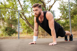 Attractive bearded young sportsman doing push-ups outdoors
