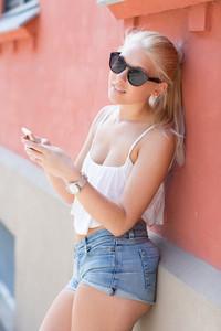 Attractive blonde teenage girl using smartphone