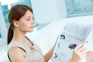 Attractive business lady with a newspaper being absorbed in her thoughts