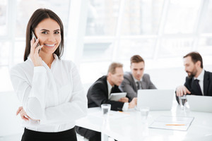 Attractive Business woman talking at phone with colleagues on background in office