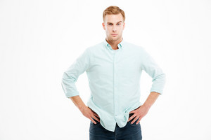Attractive confident young businessman standing with hands on hips over white background