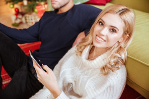 Attractive couple in sweaters sitting near the sofa with phone. cropped image