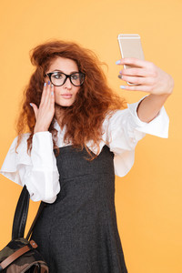 Attractive curly young woman in glasses with backpack taking selfie using smartphone