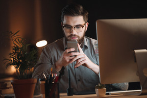 Attractive designer dressed in shirt and wearing eyeglasses working late at night and chatting by phone.