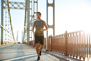 Attractive fit man running fast along big modern bridge at sunset light