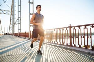 Attractive fit man running fast along big modern bridge at sunset light