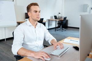 Attractive focused young businessman sitting in office and using computer