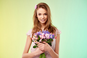Attractive girl with fresh bouquet looking at camera