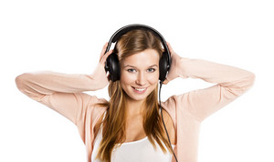 Attractive girl with headphones on gray background
