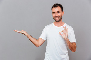 Attractive happy smiling casual young man in white t-shirt holding copyspace on palm and showing okay gesture over gray background