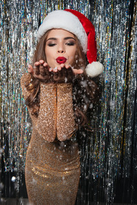 Attractive playful young woman in santa claus hat blowing on smowfalkes over shining background