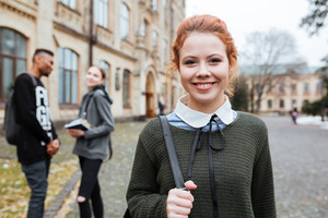 Attractive redhead woman student with backpack standing outside at the campus and looking at camera